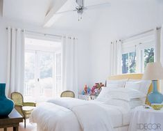 Sarah Jessica Parker and Matthew Broderick's laid-back Bridgehampton master bedroom mixes crisp white walls, bedding, and curtains with colorful accessories, including an aqua Christopher Spitzmiller lamp and apple-green vintage armchairs. Designer Eric Hughes grounded the room with a sisal rug and hung grommeted IKEA curtain panels for a relaxed, beachy feel. Tour this house.    - ELLEDecor.com
