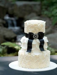Black Tie wedding cake. Small three tier wedding cake with white spirals and petals, black bow