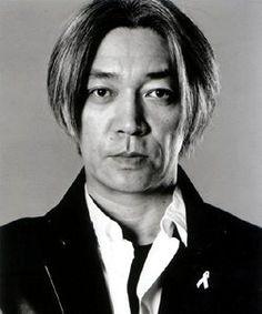 """Cet homme est très important au Japon, et vous allez vite comprendre pourquoi. Il vient d'abord d'une célèbre famille d'éditeurs. Puis très vite, ses talents pour le piano l'amène à faire partie du groupe très populaire """"Yellow Magic Orchestra"""" (YMO) avec deux autres artistes:Haruomi Hosono et Yukihiro Takahashi. Ce groupe mêle musique classique, Jpop...Le succès est au rendez vous (...)"""