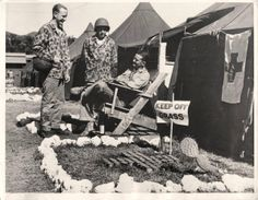 """1944- U.S. soldier relaxes in """"easy chair"""" at a Pacific base where Marine vets of the Tarawa campaign are resting. Note cactus plant, beer cans and """"Keep off grass"""" sign decorating his """"front lawn""""."""