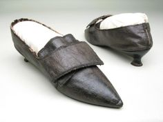 Manchester City Galleries item 1947.927,    1790-1800, Black leather, bound with black silk ribbon over glazed natural linen.    Pointed toes. Fastening with broad straps and buckle.
