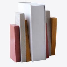 Χρωματιστοί, χειροποίητοι βιβλιοστάτες σε λιτά γεωμετρικά σχήματα που παραπέμπουν στη φόρμα των βιβλίων. Κατασκευάζονται από τσιμέντο στο εργαστήριο των We design σε σχέδιο του Σέργιου Φωτιάδη και της Ιουλίας Βλαχάκη.