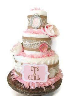 Este elegante Shabby Chic Boutique estilo pañal la torta es el perfecta centro de mesa para el próxima temática baby shower se destacan!  SHABBY CHIC PAÑAL TORTA INCLUYE: ------------------------------------------------------------------------------------------------ 40-45 pampers pañales desechables de arrullos de tamaño 1 (8-14 lb) Calidad de arpillera decorativos, cintas, arcos y perlas Es un signo de chica Coordinación de flores Decorativos personalizados personalizado inicial marco-por…