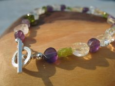 Created with Amethyst, Peridot, Citrine and Moonstone coins, this bracelet is truely OOAK!  The coins range in size from 4mm to 9mm and are paired with two sterling silver 2mm beads and a sterling silver toggle clasp.  The bracelet measures 7 1/4inches.