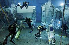 Water walk: Trainee cosmonauts, assisted by scuba divers, learn skills among the huge underwater module -- looks like fun!