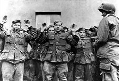 """Pvt Herbert Norman, 194th Regiment, 17th Airborne Division, is obviously amused with his catch, a batch of teenage German army soldiers happy to be captured and looking inquiringly at their smiling captor. Norman is armed with an M3 SMG known as the """"grease gun"""" in GI parlance. Location is Muenster, Germany on April 19,1945 (11 days before Hitler shot himself)."""