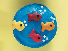 Frost cupcake with blue frosting. Attach colored Goldfish crackers to the cupcake. Use chocolate frosting to pipe eyes on fish. Add white candy confetti for bubbles