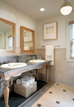 Two sinks were cut into an old table with a zinc top to create the vanity for the teen's bathroom. The mirrored medicine cabinets are sunk into the wall to provide additional storage, and the limestone used on the floors is repeated in the wainscoting.