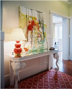 This foyer bursts with color and style. Beautiful print, coral lamp and elephant console.