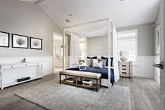 The arched ceiling of this bedroom is perfect for this abnormally tall canopy bed. A simple sheer white curtain is draped across the center of the bed, drawing the eye back down from the ceiling.