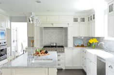 Gorgeous white kitchen  white shaker cabinets accented with nickel hardware marble subway tiled backsplash. drawers is framed by a marble herringbone backsplash and paneled range hood with built-in spice cabinets. The farm kitchen sink is flanked by a stainless steel dishwasher across from the marble topped kitchen island with undermount prep sink and bridge faucet. A wall of cabinets opposite the island highlights the stainless steel wall oven set below an integrated microwave.