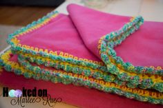 Pink fleece throw with multi-colored crochet edging in pink, purple, yellow, and teal