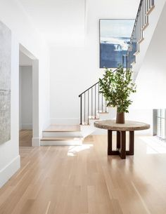 A round metal and concrete foyer table sits on wood floors under a staircase finished with an iron handrail, iron spindles, and wood treads while the wall behind it showcases a large blue abstract art piece.