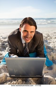 Young smiling businessman lying on a beach towel - Wavebreak Media