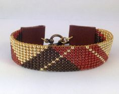 Loom woven beaded cuff bracelet, gold, matte copper and African Sunset red 11/0 glass seed beads, leather tabs and brass toggle clasp.