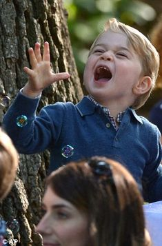 Britain's Prince George plays with bubbles