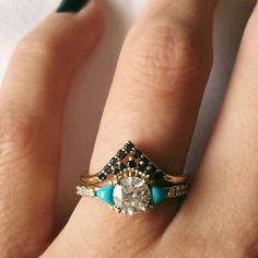 Here's an alternative bridal stack to getcha over the hump!   Turquoise trillions flank a .71 ct diamond topped with a dianty black diamond crown. We paired it with a black diamond triangle nesting ring.  This set is available, though I will be sad to see this beauty go!  DM me if you would like additional details/pricing. #loveyourbones⠀ .⠀ .⠀ .⠀ .⠀ .⠀ .⠀ #alternativebridal #indiebride #bohobride #festivalbride #altbride #shesaidyes #blackdiamond #diamond #14k #yellowgold #finejewelry…