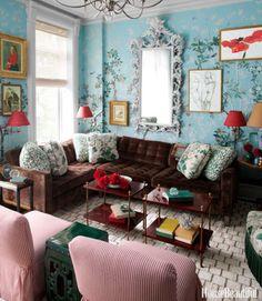 "In a Brooklyn townhouse, Iksel's Eastern Eden wallpaper turns the family room into a bower. The Climate sectional by Dune is covered in Callahan Velvet from Lee Jofa. Throw pillows in Rose Cumming's Sabu and Lee Jofa's Hollyhock. Touches of red — in the ticking stripe on the chairs, in the swing-arm lamps and chandelier by Visual Comfort — ""make the room feel festive,"" says designer Miles Redd."