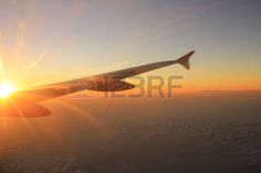 Wing of the plane lit by the sunset on a background of sky