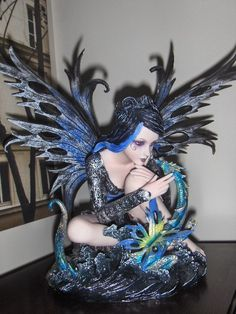 second statue is a beautiful fairie with a little dragon coloured in blues and teals and green - very peacock colours
