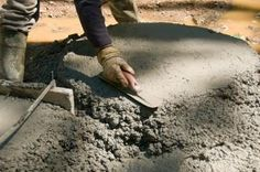 Pour concrete into holes to anchor the swing set.