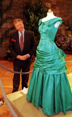 James Whitaker (Royal reporter) inspects a green gown of Princess Dianas at the Christies auction in 1997.