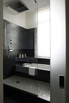 Une cloison de verre trempé et une porte en verre sablé assurent l'intimité et la luminosité de la salle de bain carrelée d'anthracite. Elle...