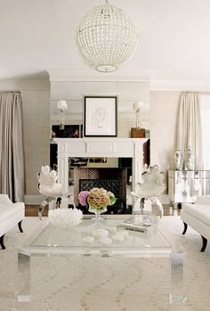 mirrored mantle + light fixture + lucite coffee table + creamy white walls and drapes