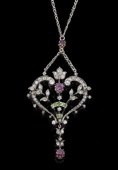 A belle époque gem-set pendant necklace, circa 1900 The heart-shaped pendant set throughout with rose and old brilliant-cut diamonds, highlighted by circular-cut rubies and demantoid garnets, suspending a later similarly-set drop, mounted in silver and gold, to a bi-coloured fetter-link chain, old brilliant-cut diamonds approx. 0.70ct total, lengths: pendant 6.1cm, chain 39.3cm, cased