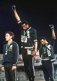 The 1968 Olympics Black Power salute was an act of protest by the African-American athletes Tommie Smith and John Carlos during their medal ceremony at the 1968 Summer Olympics in the Olympic Stadium in Mexico City. As they turned to face their flags and hear the American national anthem (The Star-Spangled Banner), they each raised a black-gloved fist and kept them raised until the anthem had finished. Clarksville, TX