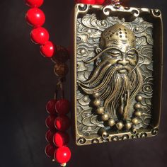 """This is our Red Cinnabar Beaded Necklace with Bodhidharma Pendant. Bodhidharma was a Buddhist monk who lived during the 5th or 6th century. He is traditionally credited as the transmitter of """"Chan Buddhism"""" ( Zen Buddhism) to China, and regarded as its first Chinese patriarch."""