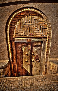 Traditional old wooden door and mud frame arches in the Ancient city of Yazd, Iran