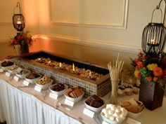 S'mores bar. LOVE the lanterns hanging on mini shepherd's hooks in flower planters! Too cute.