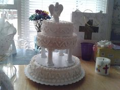 The cake I made for Aubrey for First Communion. The statue on top I bought at Hallmark it is not a cake topper. To protect the statue from the buttercream icing, I put a tiny piece of plastic wrap the same size of the statue under it. Worked great. Now she has an extra keepsake too.