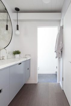 Long and narrow bathroom features a gray floating vanity topped with gray and white marble under an oversized antiqued convex mirror next to a water closet.
