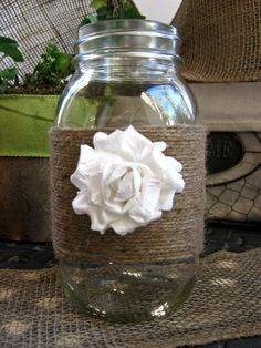 Mason jar centerpieces wrapped in burlap with fabric flower on two sides