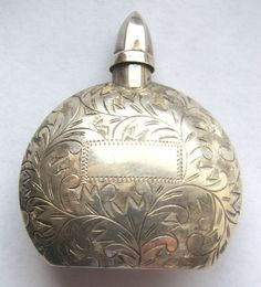 """Here is a lovely vintage perfume bottle marked on the bottom """"Sterling 950."""" It has a substantial amount of floral etching on a place where it can be monogrammed. The dauber is intact. This lovely piece measures 1 7/8"""" by 1 1/2"""" (with the lid on). It has a pillowed shape, deepest at the center and tapering off to the sides. Condition is very good! I see it for sale on the net for One hundred twenty eight dollars to two hundred and ninety nine dollars..."""
