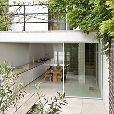 A work surface runs from the garden into the kitchen of this home, creating a seamless space that blurs the distinction between inside and out.