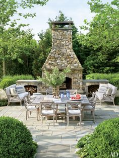 Country Casual sofas and chairs cushioned in a Sunbrella fabric are arranged near the outdoor fireplace on the terrace of a Southampton, New York, home devised by architect John David Rose and Carrier & Co. Interiors.