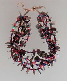 """Necklaces have been made like this in the """"New World"""" since coins were first minted there.  This necklace has four loops of strands with more than 120 coins from Peru, Colombia and Ecuador generally from the 1940s to 1960s.  The strands are tied together at the back.  This necklace would have been worn with traditional clothing for special occasions, market visits, or church visits. 
