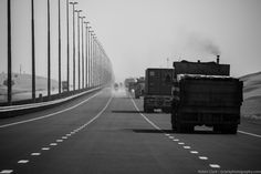 One of the major motorways in Dubai extending into the desert with a seeming endless line of lorries.