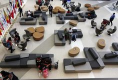 Travelers sit on stylized chairs and ottomans in a waiting area of the Tom Bradley International Terminal at Los Angeles International Airport. Dining Room Bench Seating, Storage Bench Seating, Cafe Seating, Restaurant Seating, Bedroom Seating, Public Seating, Outdoor Seating Areas, Lounge Seating, Office Lounge