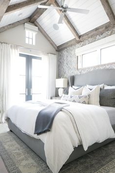 This unique bedroom features a wooden herringbone patterned accent wall, french doors to a balcony, exposed wood beams on the ceiling, and queen sized bed.