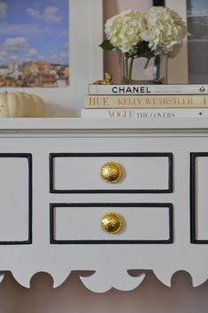 credenza makeover with three coats of shiny white paint, navy trim and gold knobs.