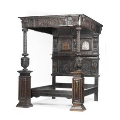 A fine Elizabethan style carved oak tester bed the headboard with arched panels, foliate inlay, and with acanthus terminals centred by a caryatid, the tester with segmented panels, inlay and four turned bosses, the side friezes centred by lion masks, the end frieze with caryatid and strapwork panel, the bed end with twin turned ornate posts on square pedestals