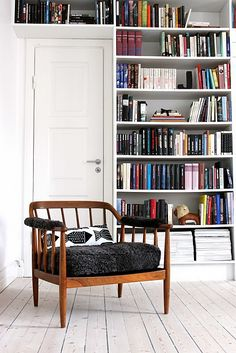 White room with black accents....and color-coded bookshelves!