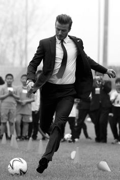 Not just David Beckham, David Beckham in a suit playing soccer.