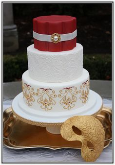 White and burgundy Venetian masquerade wedding cake with red Swarovsky crystals and gold embossed mask