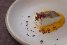 """Baccalà alla carbonara.  Un piatto molto creativo che racconta la passione dello Chef Marcello Trentini per la cucina romana. La base del piatto è uno zabaione a base di brodo di pollo e pecorino fornito in sac à poche e pronto ad essere impiattato. Il baccalà cotto a bassa temperatura dal ristorante, sarà solo da rigenerare. Infine, la """"sabbia"""" di prosciutto, ottenuta disidratando il prosciutto crudo di Parma, guarnirà il piatto."""