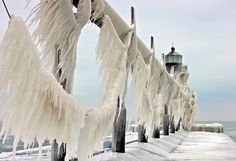 """Ice formed on the St. Joseph, Michigan lighthouse and catwalk during a winter storm that churned up Lake Michigan and created 20 foot waves. The ice apparently broke the """"hand rail"""" cables on the catwalk, and they are drooping down with tons of ice. – Frozen World photographed by Tom Gill"""